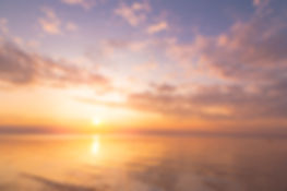 Calm sea with sunset sky and sun through
