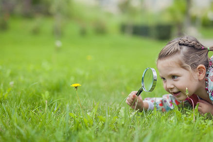 Little cute girl with magnifying glass l