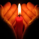 hands holding a burning candle in dark l