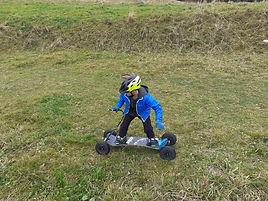 Photo d'un jeune pratiquant la mountainboard de descente sur le Revard