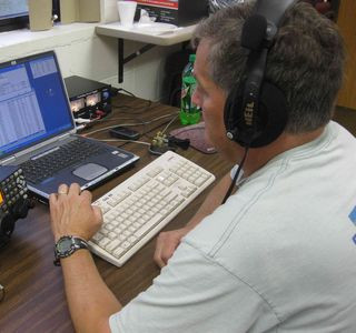 Jasper of Plover operates the Morse code station. Code can be sent either on the keyboard or via a 'paddle' seen to its right. The transceiver (left) transmits with a power of 100 watts and can be powered either from emergency sources or the commercial grid. Contacts are logged on the computer.
