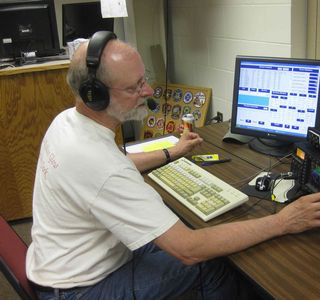 Mike Pagel of rural Amherst operates the 'phone' (voice) station. He turns the dial on his 100 watt transceiver (right) and logs contacts on the computer