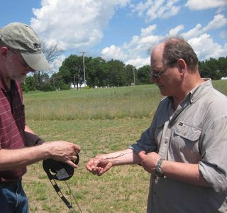 Mike Pagel and Mike Gorniak unroll a wire antenna from its spool prior to hanging it from utility poles.