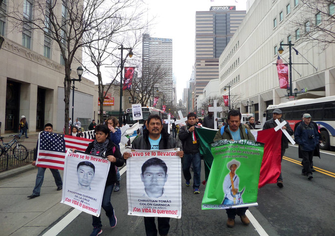 Felipe de la Cruz Sandoval, spokesman for the relatives of the normalistas, and graduate of the Ayotzinapa Rural Teachers' College, marches in New York City with a banner for Christian Tomás Colón Garnica, April 2015; with Anayeli Guerrero de la Cruz (sister of Joshivani Guerrero de la Cruz, cousin of Emiliano Alen Gaspar de la Cruz and Everardo Rodríguez Bello,) Clemente Rodríguez Moreno (father of Christian Alfonso Rodríguez Telumbre.) The march was part of the three-pronged Caravan 43 (East Coast, Midwest and West Coast,) visiting more than 40 US cities to spread the call for justice—and against US funding of the drug war in Mexico. Photo: Somos Los Otros NY