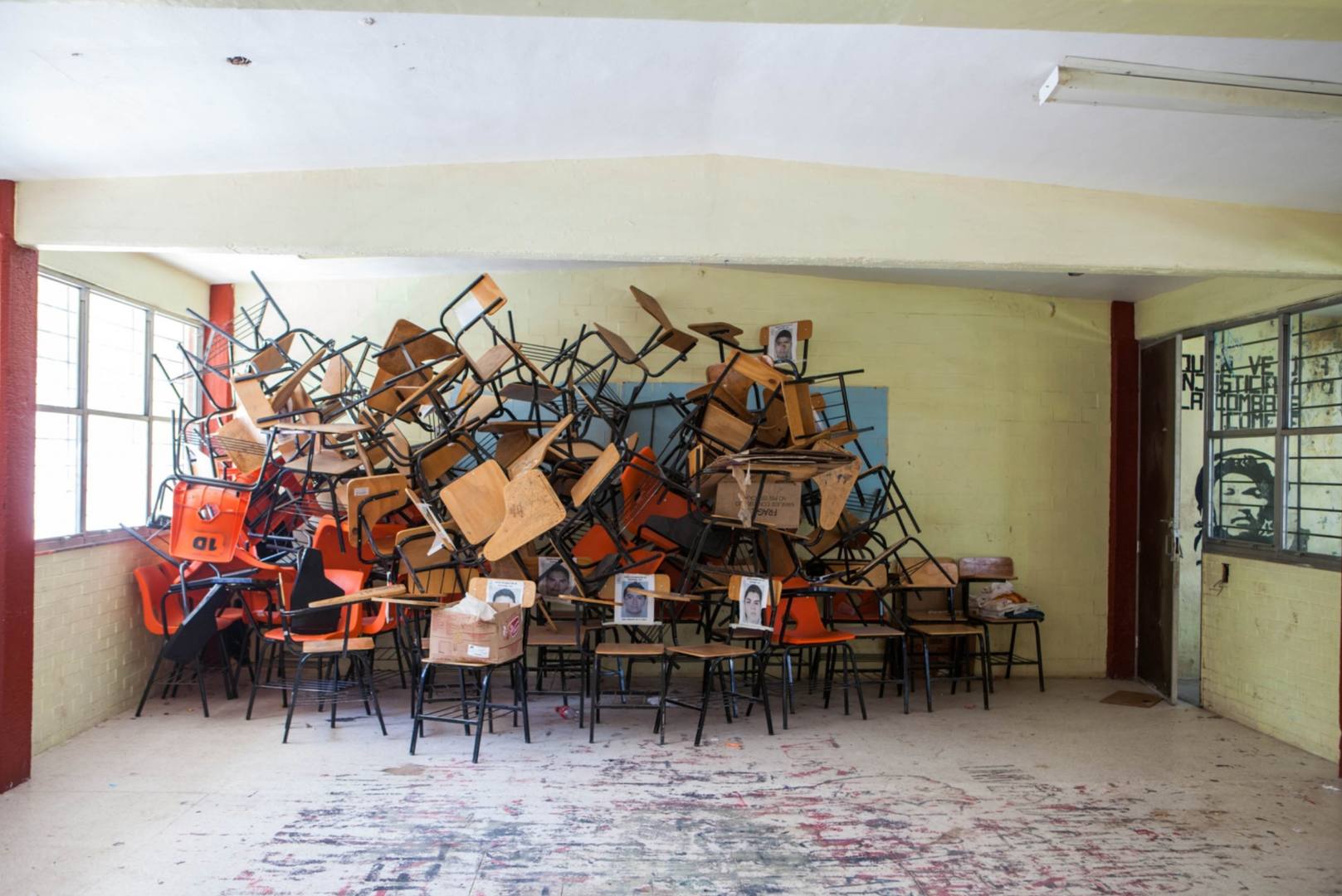 A classroom at the Escuela Normal Rural Raúl Isidro Burgosde Ayotzinapa, 2014. Chairs have been piled up to make room for sleeping quarters for the victim's familes and supporters in the months folowing the attacks of September 26-27.  Photo: Livia Radwanski