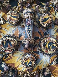 Le Lion  Masque en assemblage de tapisseries, points de Bayeux, souligné de frises passementerieset pompons, ornementéde perles plates et sequins noirs, sur châssis.