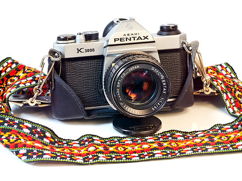 Pentax K1000 with lens, strap and half case front view