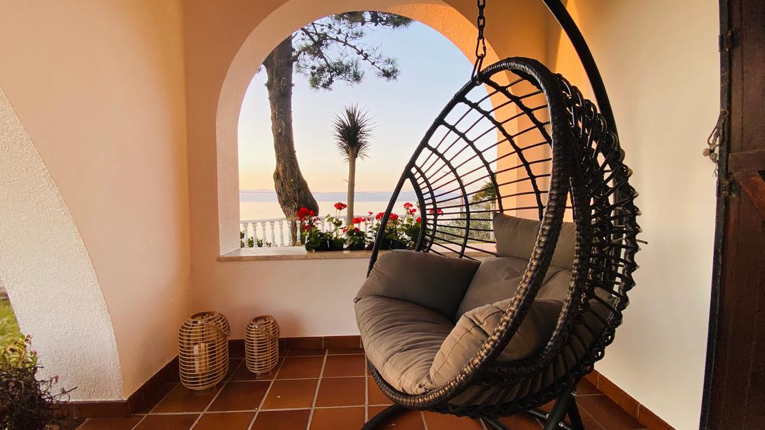 Terraza con sillon colgante sobre el mar
