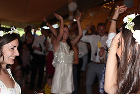 Bride, Bridesmaids & rest of crowd dance at a Tipi Wedding Reception in Oakhampton Rutland.