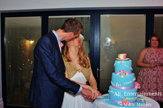 Bride and Groom Kiss as They Cut Their First Cake