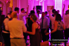 Wedding guests bathed in purple light from mobile DJ.