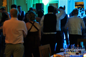 Packed dance floor in front of wedding DJ.