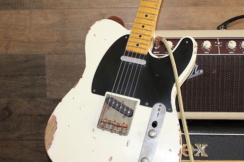 A white & weathered Fender Telecaster guitar used to represent indie, rock & alternative music.