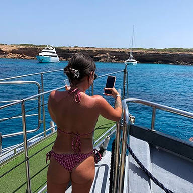 girl taking pictures of yachts in ibiza.