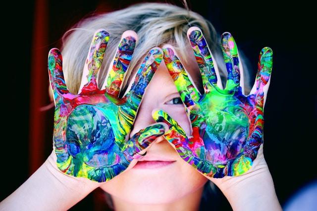 Glückliches Kind mit bunter Farbe an den Händen