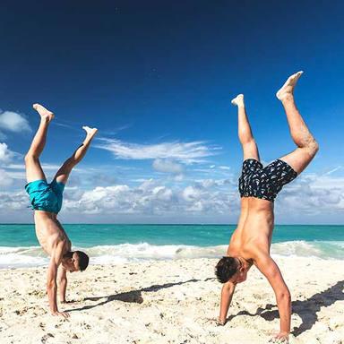 men on beach hand stand formentera.jpg