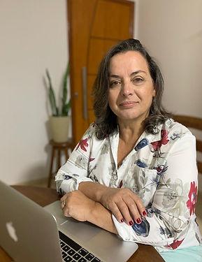 Foto de Marilza Loubach sentada à mesa com um notebook aberto olhando à frente.