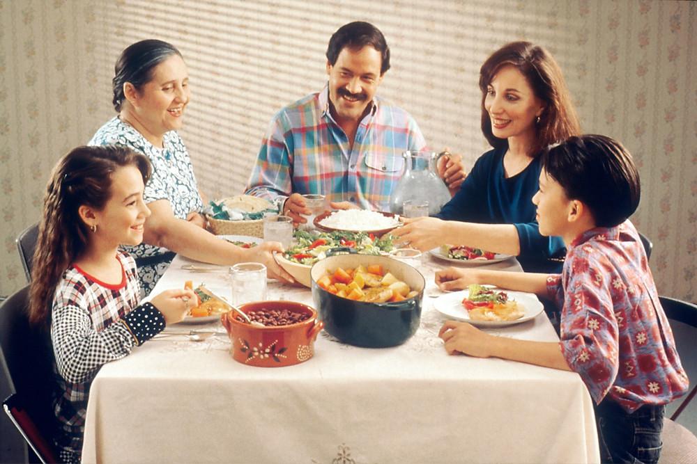 Uma familia hispânica  representada à mesa, num momento de jantar.