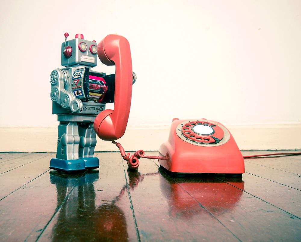 big silver robot toy on the phone standing on an old wooden floor t