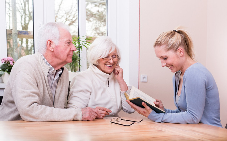 Betreuerin liest Bewohnern vor