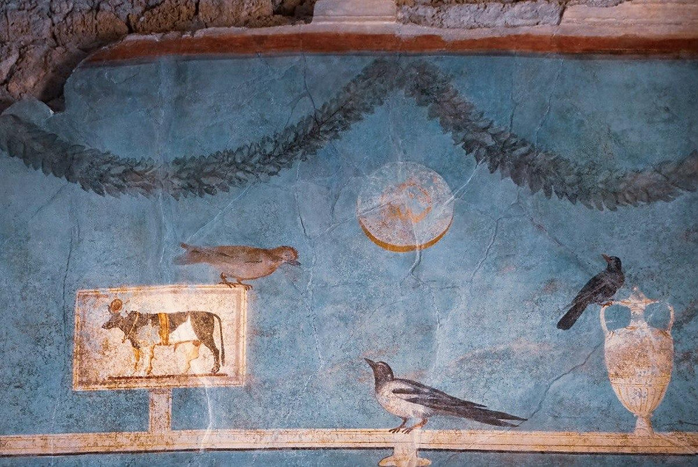 Wall painting from the House of the Orchard showing a depiction of the Apis bulls, as well as birds, a vase and garlands.
