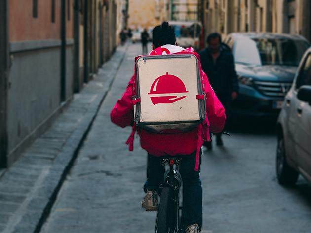 Entregador andando de bicicleta, de costas para a câmera. Transeuntes ao fundo da imagem.