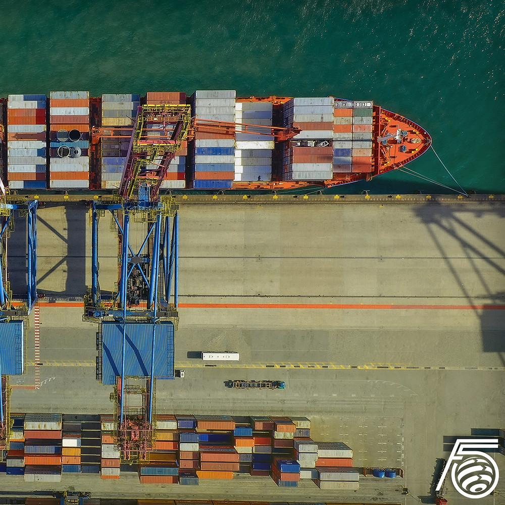 Imagem aérea de um porto com um cargueiro atracado