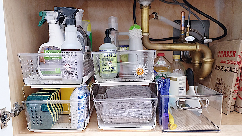 The cabinet under the kitchen sink organized with bins