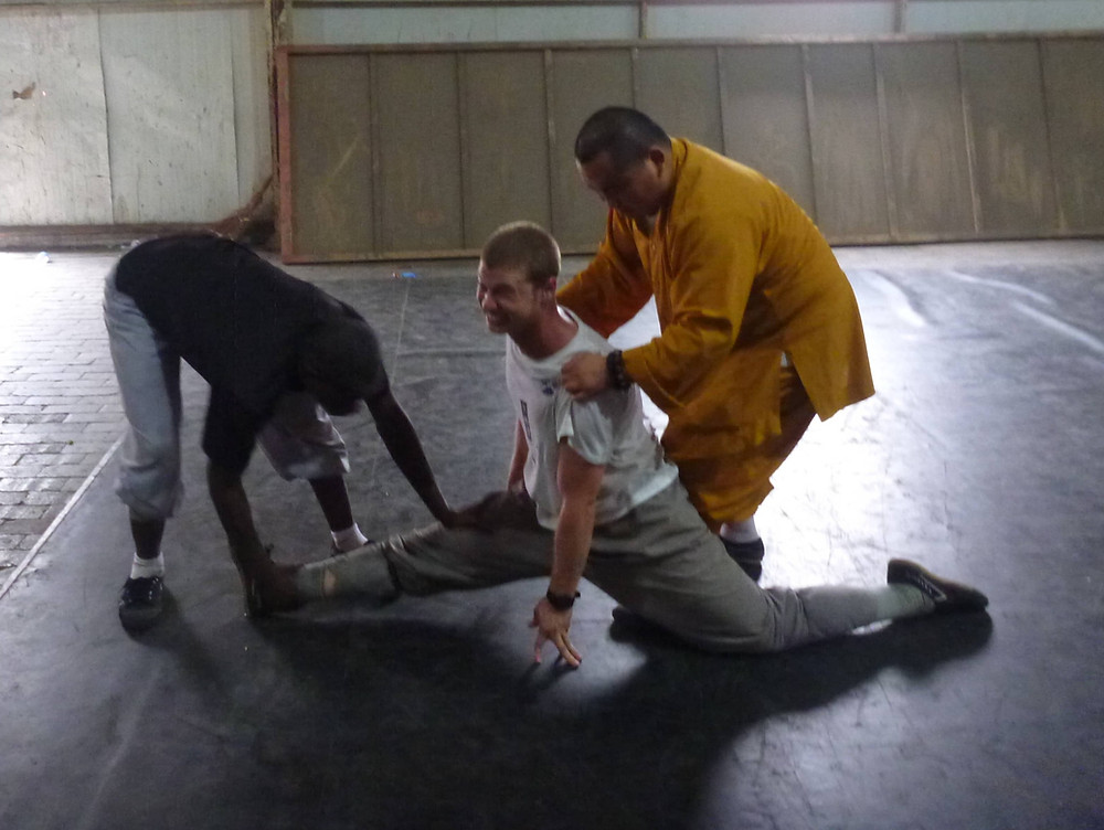 Ben stretching during training as a monk in China