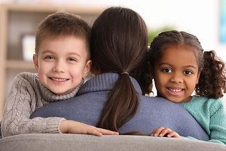 Woman hugging little kids indoors. Child