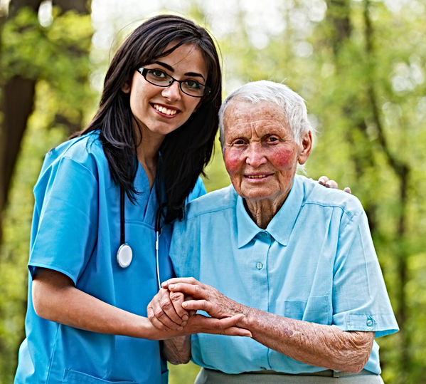 Kind nurse together with elderly woman i