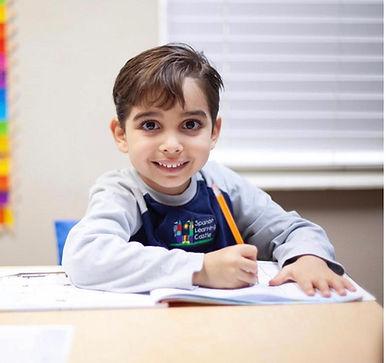 kid on desk inside smiling.jpg