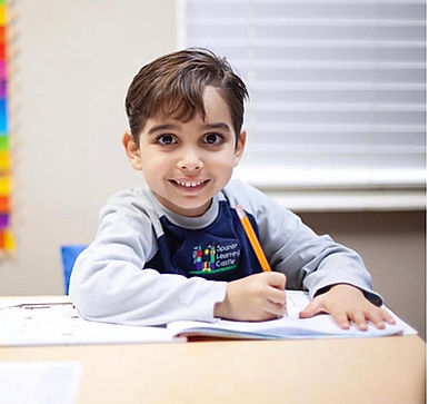 kid on desk inside smiling.jpg