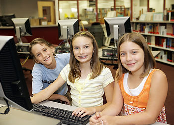 Primary school pupils working on a desktop computer and smiling