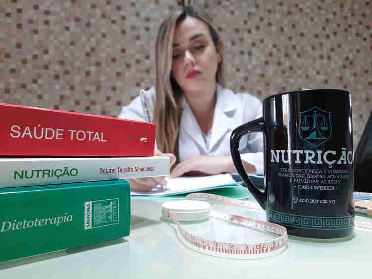 A nutricionista Larissa Moema preenche um formulário em sua mesa de trabalho. Na foto aparecem objetos de trabalho, livros de Nutrição, computador portátil e uma caneca.