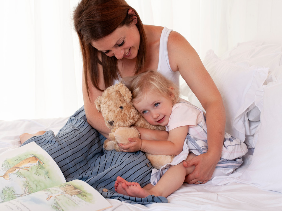 mum and baby cuddles on white studio bed natural photos