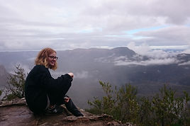 Young woman looking out over the mountains from a higher place