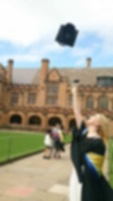 Student celebrating her graduation by throwing her mortar board in the airoutside sandstone university buildings