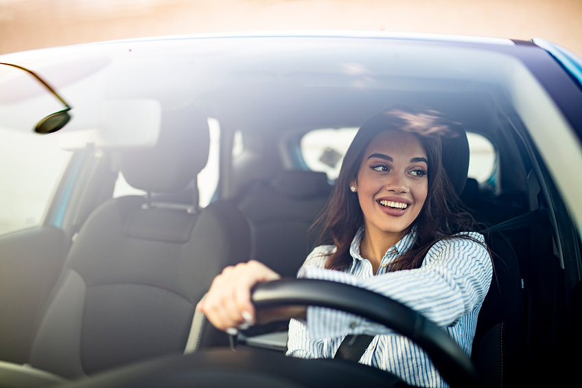 Happy woman driving a car and smiling. Cute young success happy brunette woman is driving