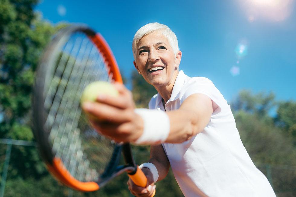 smiling-elderly-woman-playing-tennis-as-