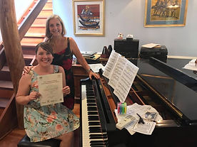 Piano Teacher Standing over Student holding a piano certificate and sitting at a grand piano