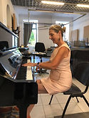 Professional pianist playing a grand piano in an elegant dress