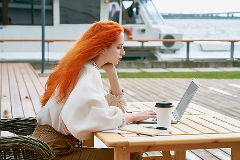 freelancer-girl-is-sitting-in-cafe-on-street-and-r-ZUXAA7W.jpg