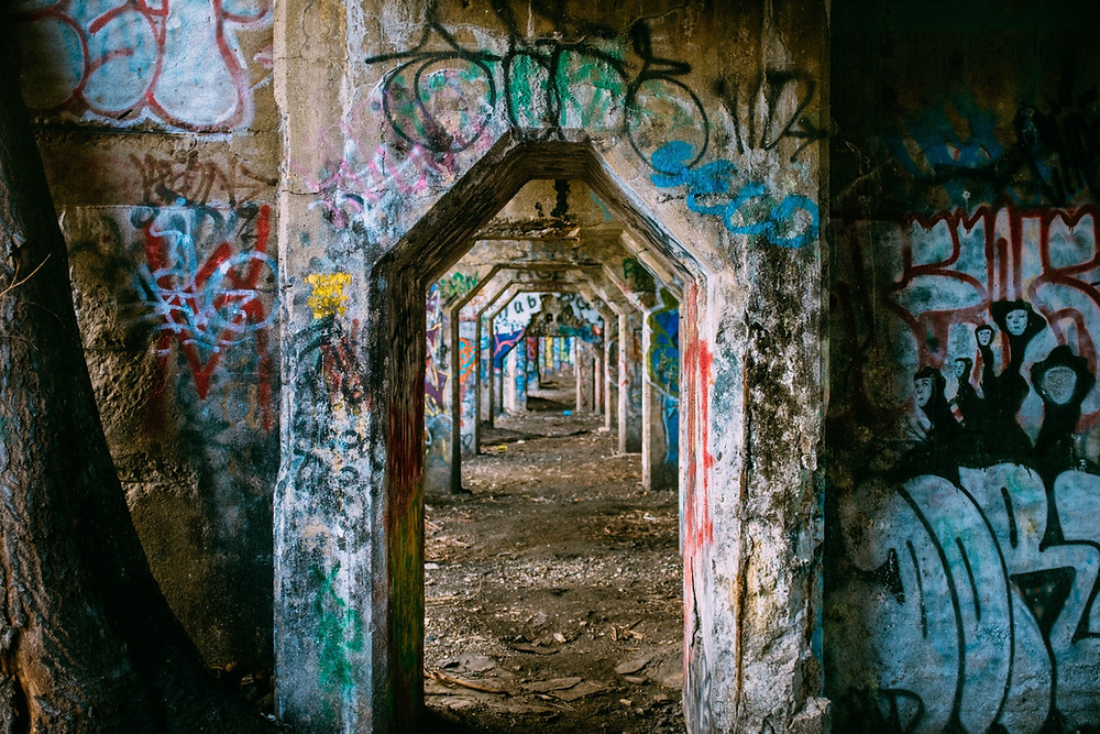 a tunnel made of cement covered in graffiti