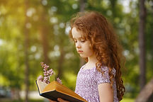 little-girl-reading-book-spring-park.jpg