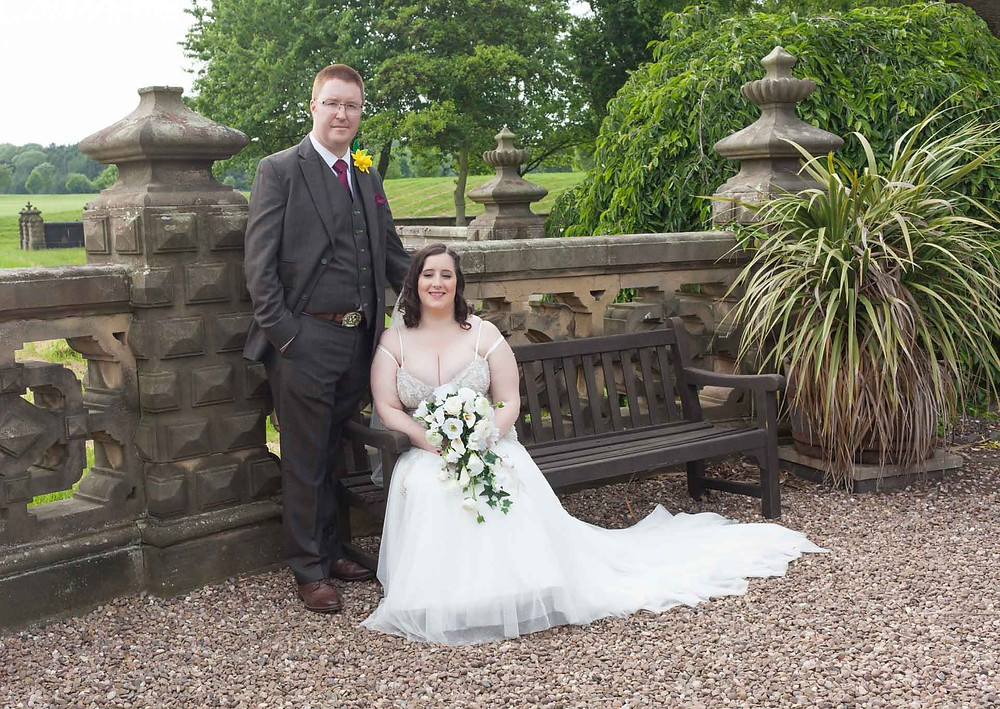 groom standing beside a bride whilst sitting on a bench