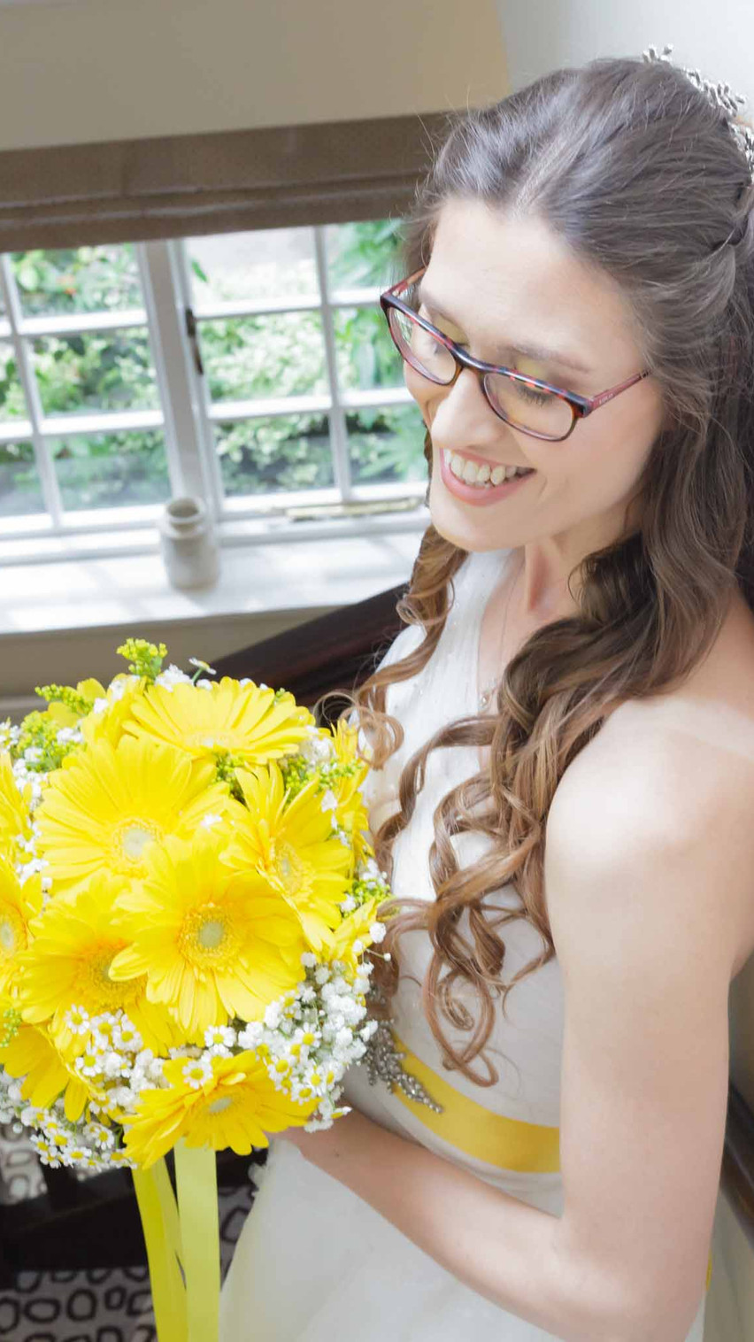 bride in a white dress on the stairs holding a bouquet of yellow flowers