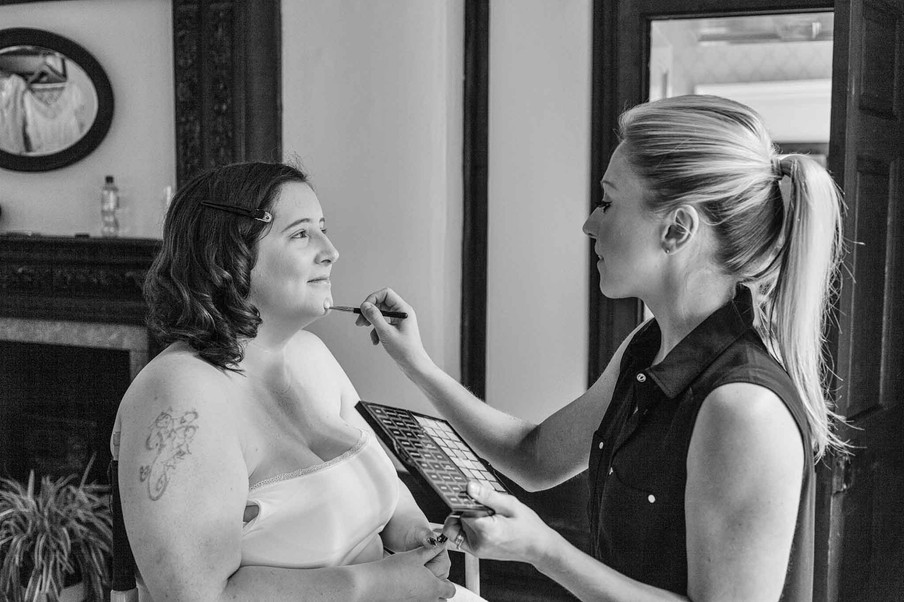 bride getting her makeup done sitting in a chair