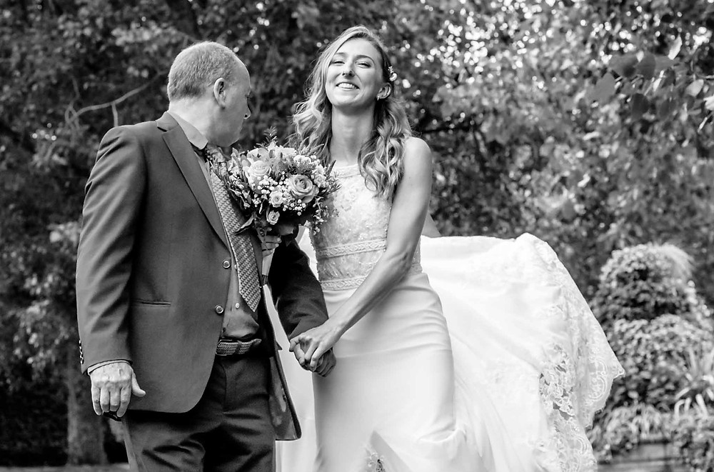 black & white image of a bride and her father preparing to walk down the aisle