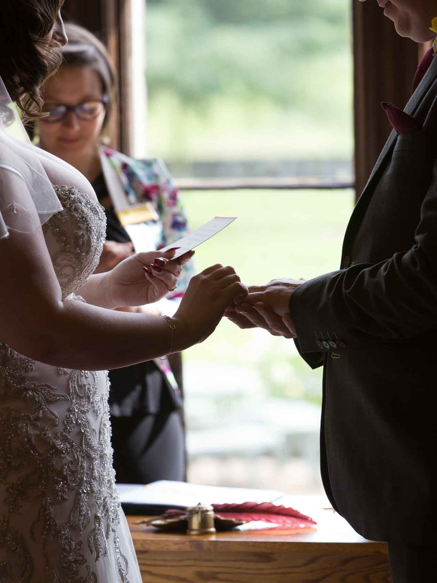 bride holding the grooms hand as she reads from a letter